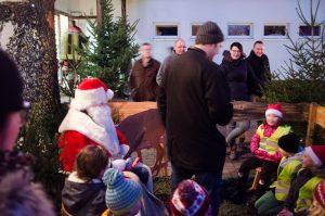 Viele Kinder tummeln sich um den Weihnachtsmann um ihr Gedicht aufzusagen