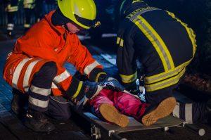 Geborgene Personen werden mit einer Trageliege zum Rettungswagen transportiert.